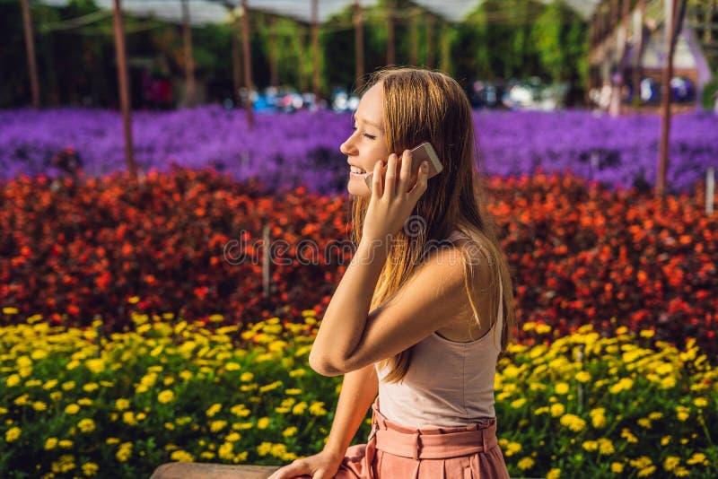 Młoda kobieta w kwiat szklarni Jaskrawy tropikalni kwiaty zdjęcia stock