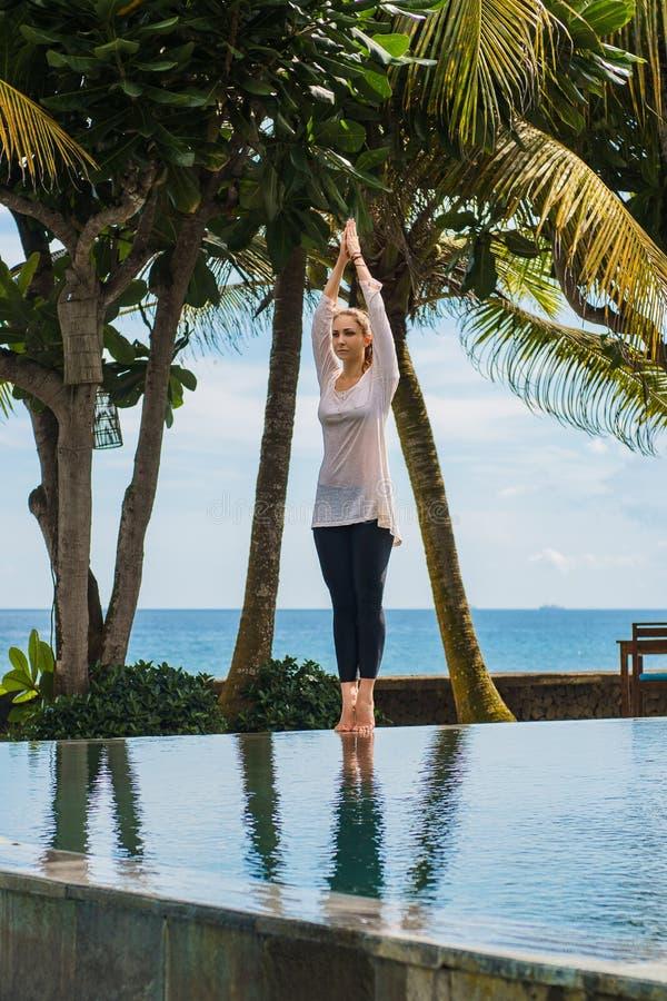 Młoda kobieta w leggings i tunice robi joga praktyce, medytacja rozciąga ręki w górę i stoi w kurorcie z oceanu krajobrazem, zdjęcia stock