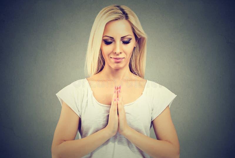 Młoda kobieta w modlitewny pozyci medytować obrazy stock