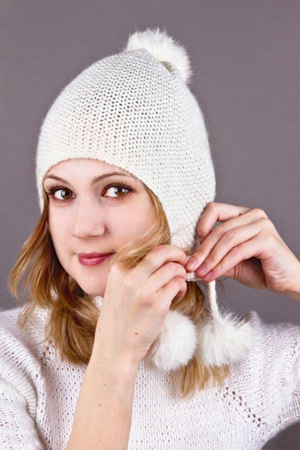Młoda kobieta w nakrętki biały trykotowym grey obraz stock