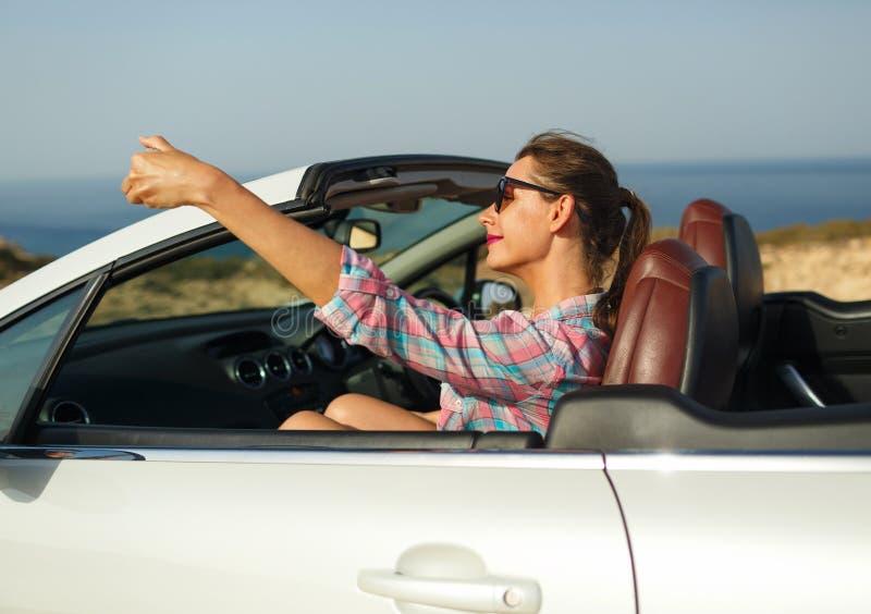 Młoda kobieta w okularach przeciwsłonecznych robi jaźń portreta obsiadaniu w ca obrazy royalty free