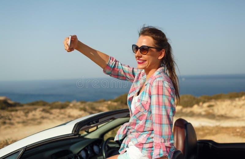 Młoda kobieta w okularach przeciwsłonecznych robi jaźń portreta obsiadaniu w ca obraz stock