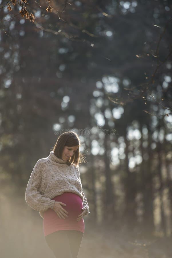 Młoda kobieta w opóźnionym ciążowym macaniu jej nabrzmiały brzuch fotografia stock
