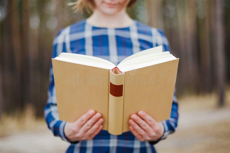 Młoda kobieta w parkowego mienia otwartej książce zdjęcia stock