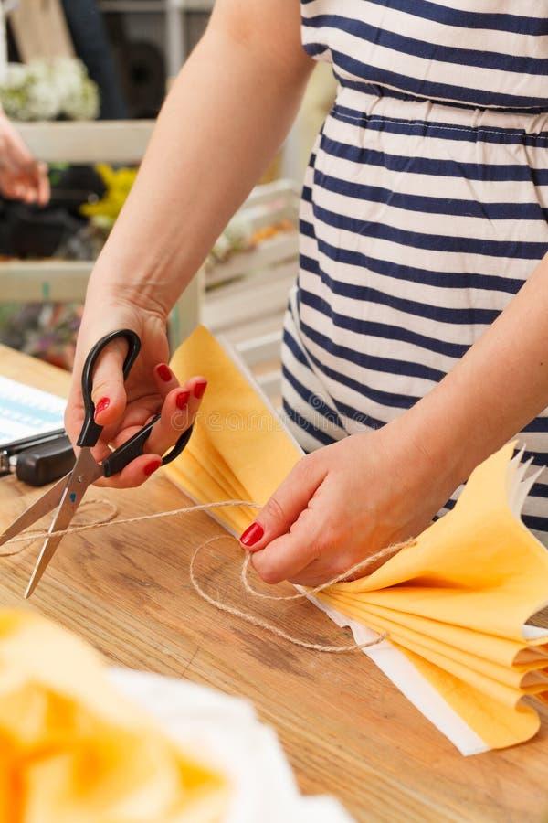 Młoda kobieta w pasiastej koszula robi żółtego papierowego kwiatu z nożycami obrazy stock