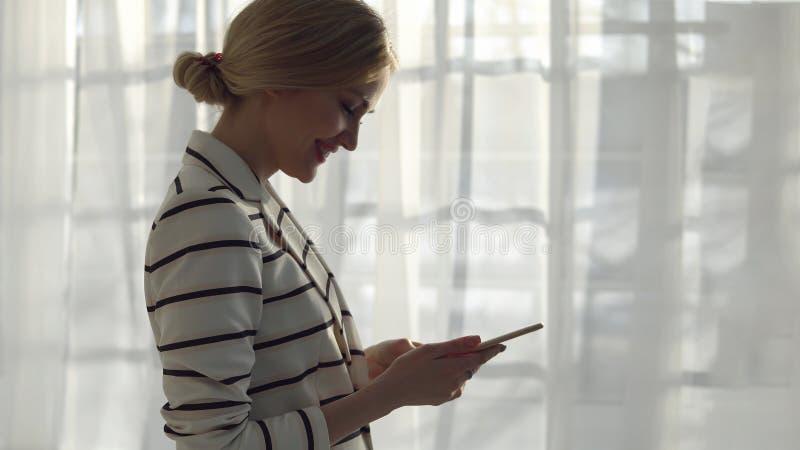 Młoda kobieta w pasiastej kurtce z telefonem na nadokiennym tle obraz royalty free