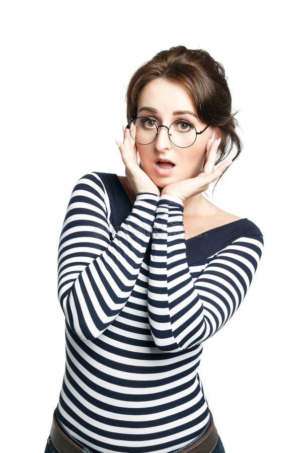 Młoda kobieta w pasiastym ciasnym pulowerze, jest ubranym wokoło szkieł, robi godny pożałowania twarzy, fotografia stock