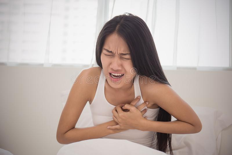Młoda kobieta w piżamach ma atak serca w łóżku obraz stock