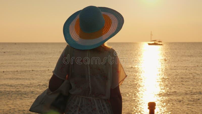 Młoda kobieta w plaży odzieżowej i być wypełnionym czymś kapeluszu cieszy się wschód słońca na seashore odosobniony tylni widok b zdjęcia royalty free