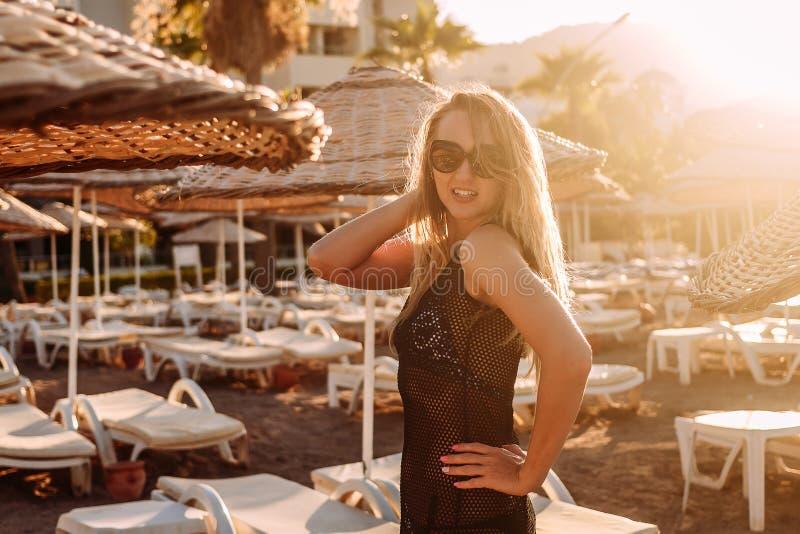 Młoda kobieta w przejrzystej tunice i okularach przeciwsłonecznych stoi blisko plażowego parasola plecy w zmierzchu świetle obraz stock