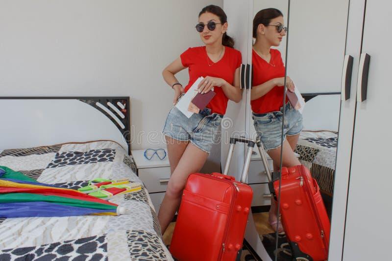 Młoda kobieta w przypadkowej pozyci z podróży walizką, mienie paszportem i biletami, zdjęcia stock