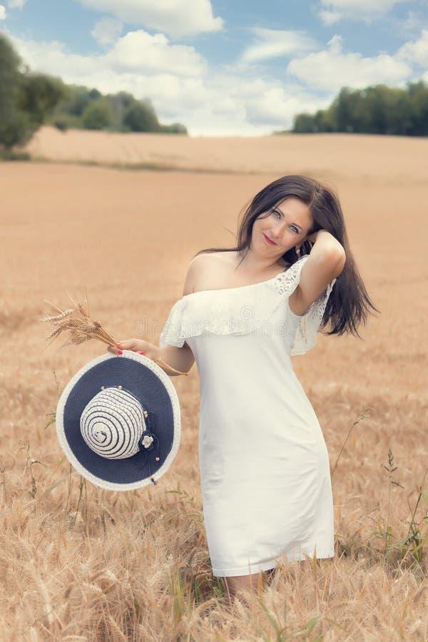 Młoda kobieta w pszenicznym polu na słonecznym dniu fotografia stock