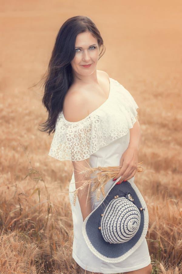 Młoda kobieta w pszenicznym polu na słonecznym dniu zdjęcia royalty free