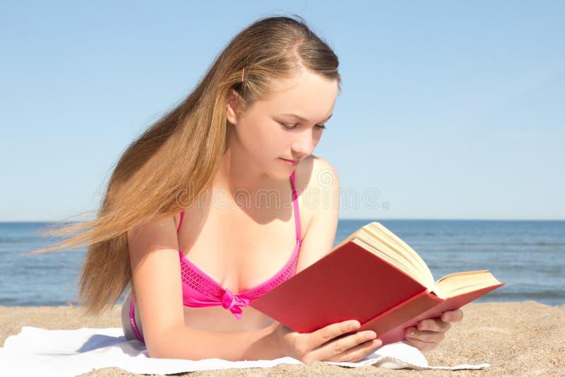 Młoda kobieta w różowego bikini czytelniczej książce na plaży obrazy royalty free