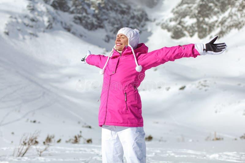 Młoda kobieta w różowej narciarskiej kurtce, rękawiczkach i spodniach, ręki rozprzestrzenia, e zdjęcie stock