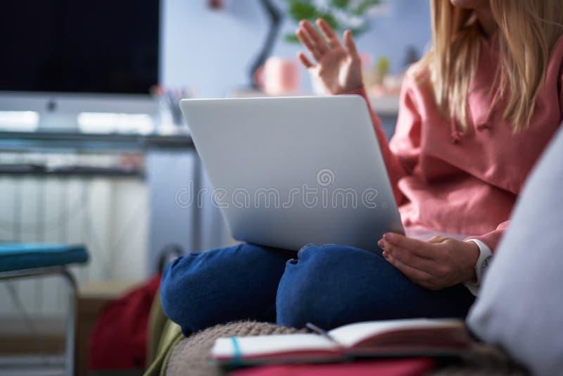 Młoda kobieta w różowym hoodie używać laptop obrazy stock