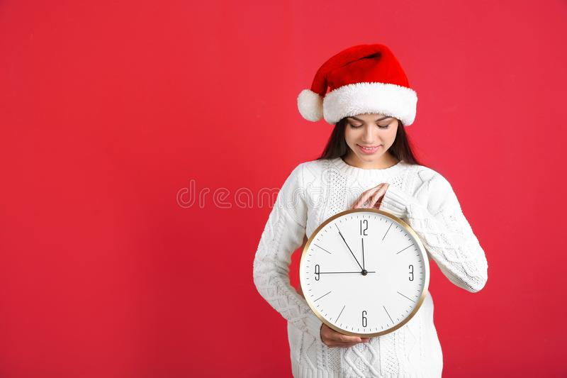 Młoda kobieta w Santa kapeluszowego mienia dużym zegarze na koloru tle świętuje świętowania bożych narodzeń córki kapeluszy macie obrazy royalty free