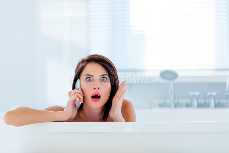 Młoda kobieta w skąpaniu z telefonem obrazy stock