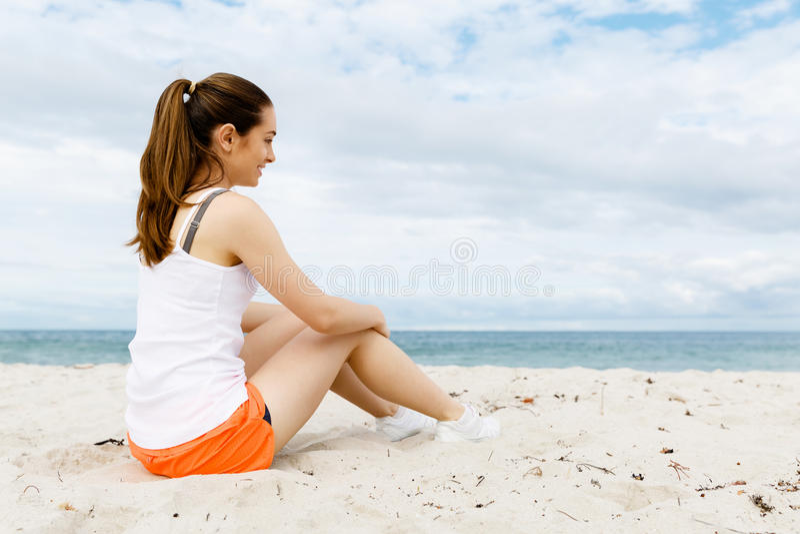 Młoda kobieta w sportach jest ubranym obsiadanie przy plażą zdjęcie royalty free