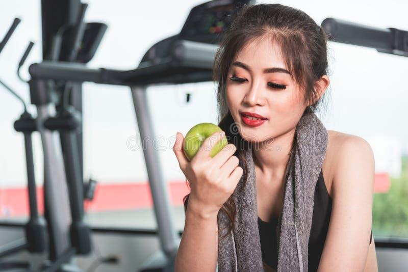 Młoda kobieta w sportswear mienia zieleni jabłku przy gym fotografia stock