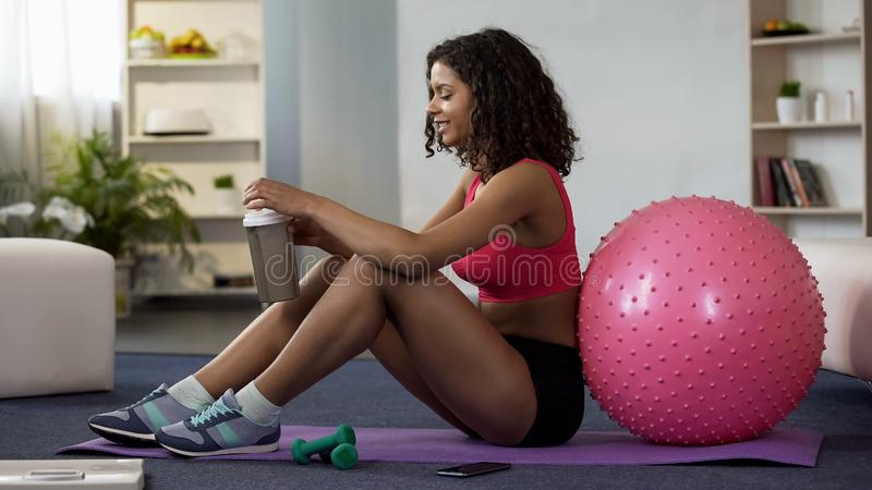 Młoda kobieta w sportswear obsiadaniu na podłoga, mienie bidon po treningu obraz royalty free