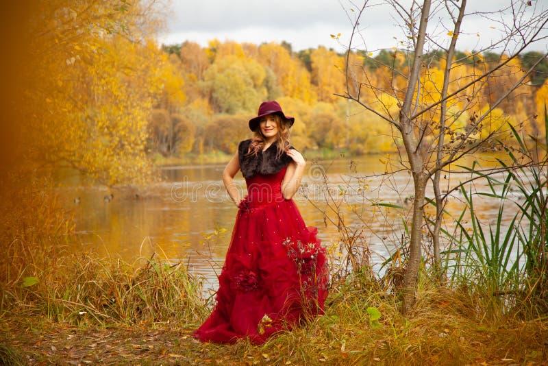 Młoda kobieta w stylowym kapeluszu i długiej czerwonej sukience wieczornej z futrzem, które pozują koło rzeki i idą w jesiennym o zdjęcia stock