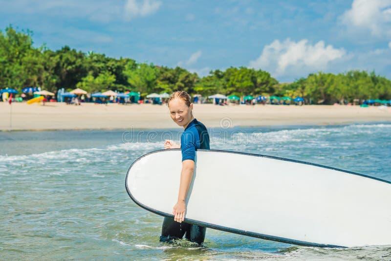 Młoda kobieta w swimsuit z kipielą dla beginners gotowych surfować pozytywne emocje zdjęcie royalty free