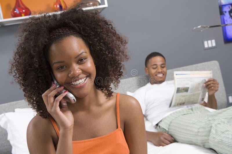 Młoda Kobieta W sypialni Używać telefon komórkowego obraz stock
