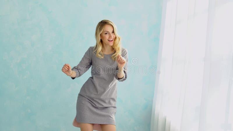 Młoda kobieta w szarej sukni tanczy przeciw błękitnemu ściennemu tłu fotografia royalty free