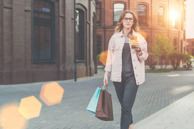 Młoda kobieta w szkłach chodzi wzdłuż miasto ulicy, niesie torba na zakupy i trzyma filiżankę kawy, fotografia royalty free