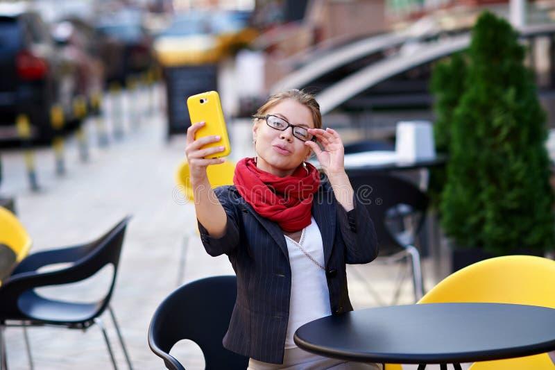 Młoda kobieta w szkłach robi selfie w kawiarni obraz royalty free