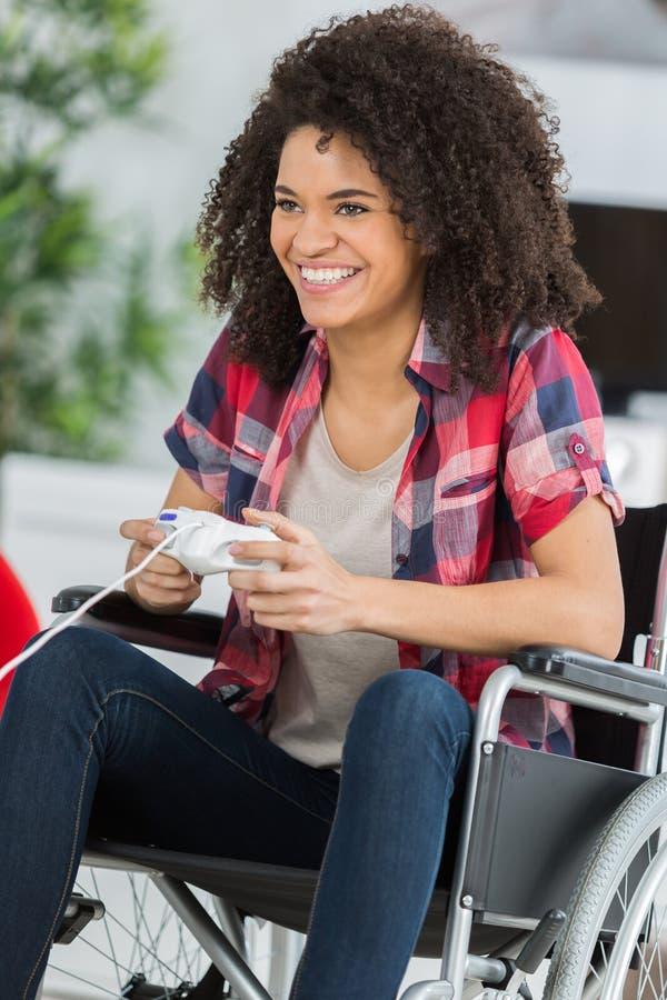 Młoda kobieta w wózku inwalidzkim bawić się wideo gry w domu zdjęcie royalty free