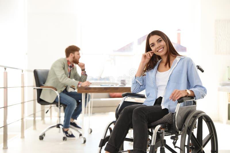 M?oda kobieta w w?zku inwalidzkim z colleagus zdjęcie stock