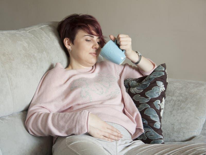 Młoda kobieta w wczesnym ciążowym obsiadaniu na leżance fotografia royalty free