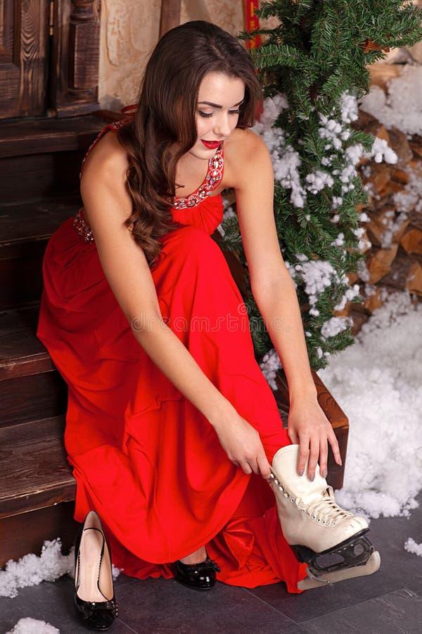 Młoda kobieta w zimy czerwieni sukni na ganeczku dekorował z Bożenarodzeniowymi dekoracjami, stawia na łyżwach patrzeje w dół zdjęcie stock