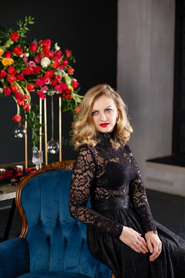Młoda kobieta weared w czarnym blisko dekorującym stole z czerwonymi kwiatami obraz stock