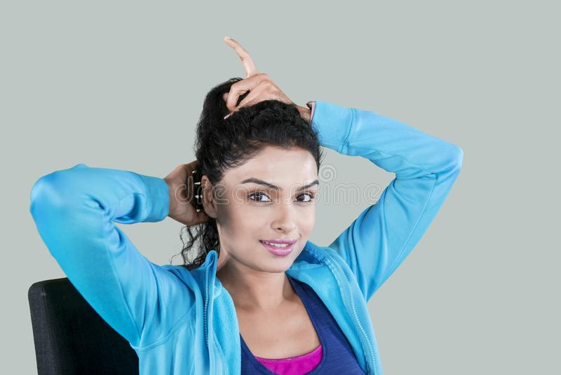 Młoda kobieta wiąże jej kędzierzawego włosy w studiu zdjęcie royalty free