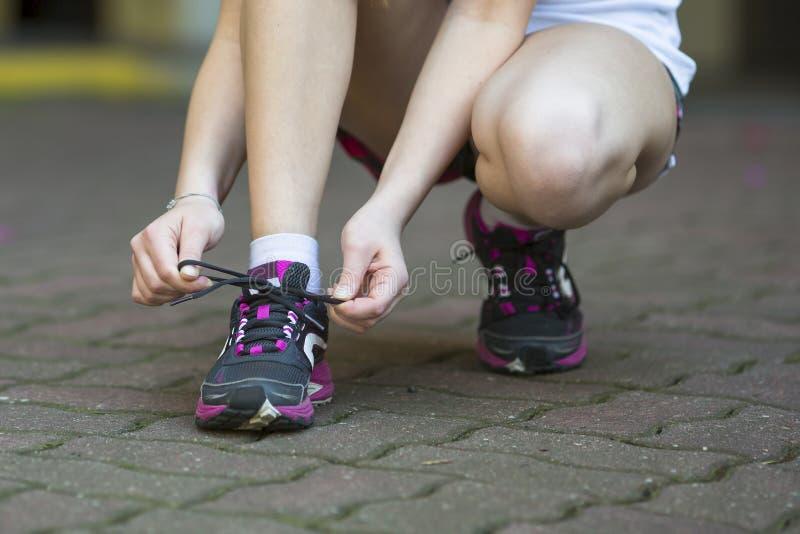 Młoda kobieta wiąże koronki przed biegać obrazy stock