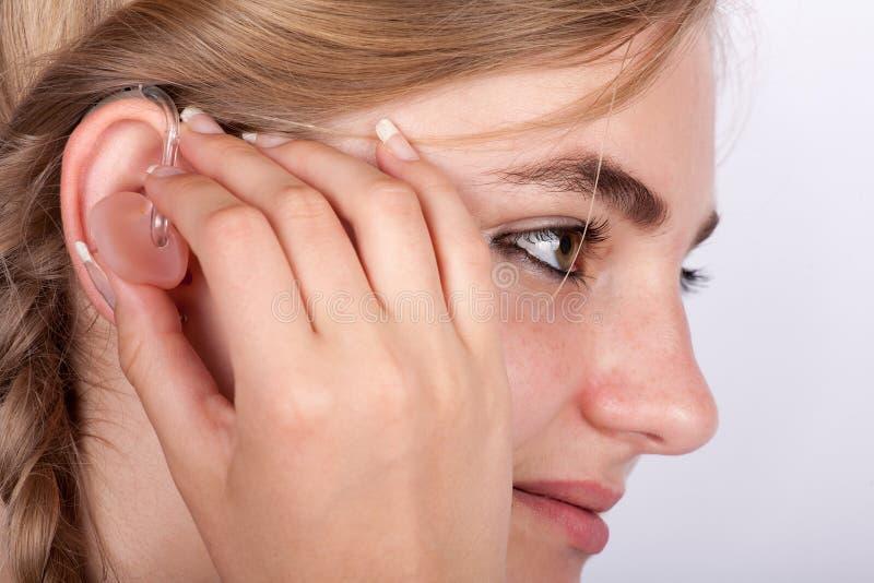 Młoda kobieta wkłada przesłuchanie pomoc w jej ucho zdjęcie royalty free