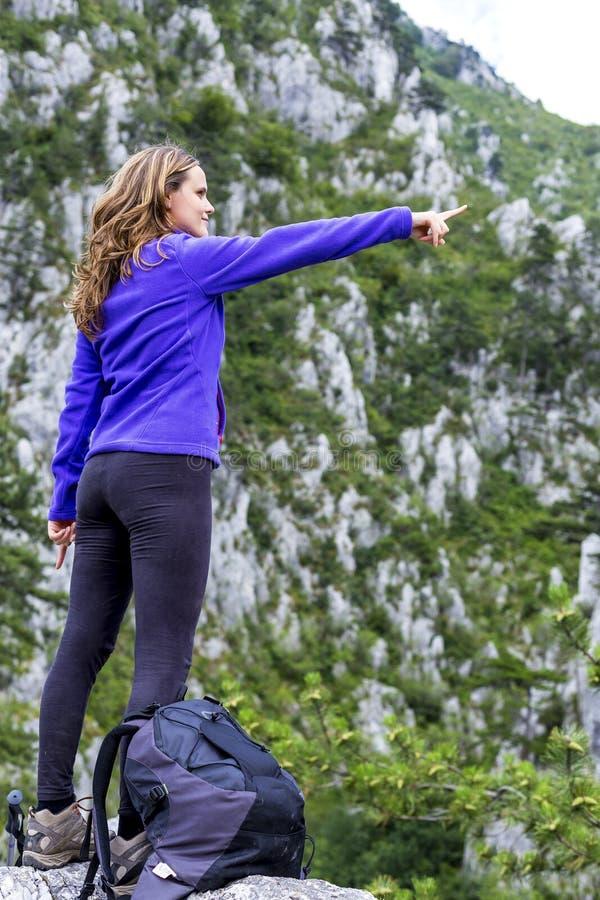 Młoda kobieta wskazuje podczas gdy stojący na skale przeciw zadziwiać zdjęcie royalty free