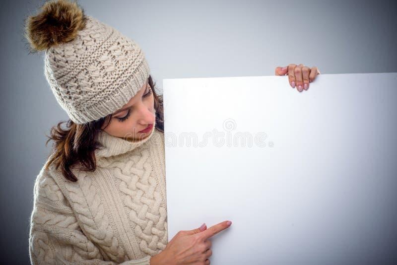 Młoda kobieta wskazuje znak w zimy modzie fotografia stock