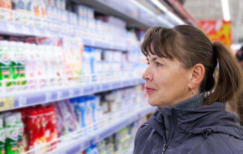 Młoda kobieta wybiera świeżego mleko produkuje zdjęcie royalty free