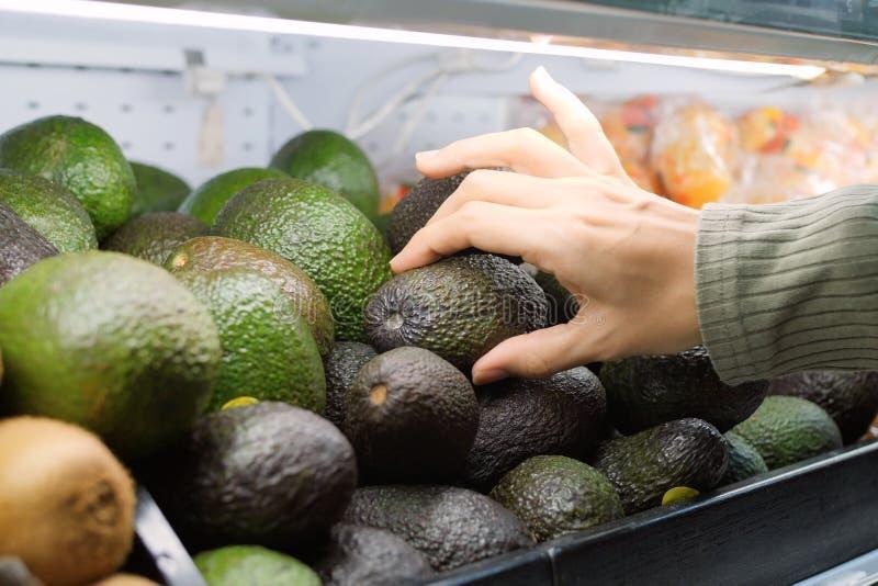 Młoda Kobieta Wybiera Avocados w sklepie spożywczym Weganinu Zero dziewczyny kupienia Jałowe owoc i Veggies w Organicznie superma zdjęcie royalty free