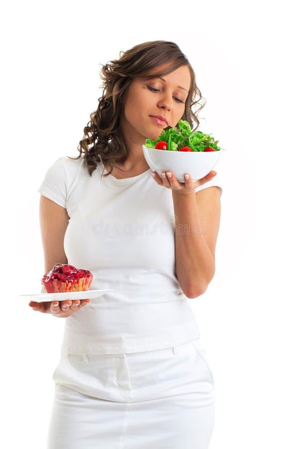 Młoda kobieta wybiera cukierki lub zdrowego łasowanie zdjęcie stock