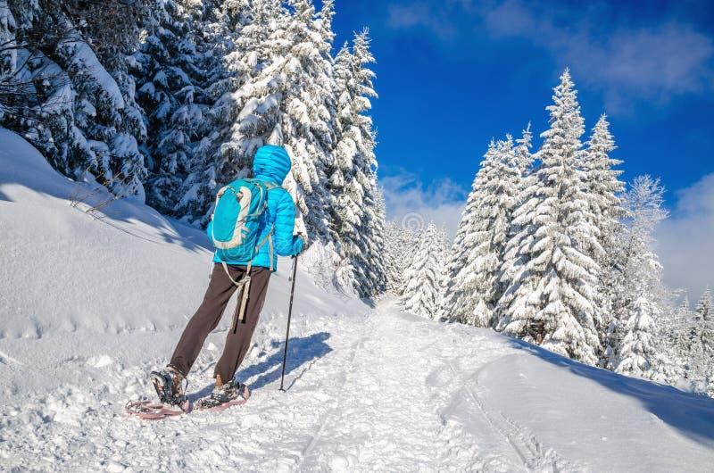 Młoda kobieta wycieczkuje na śnieżnych butach w jutrzenkowej kurtce fotografia stock