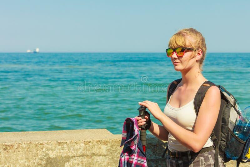Młoda kobieta wycieczkuje na dennym wybrzeżu z plecakiem fotografia stock