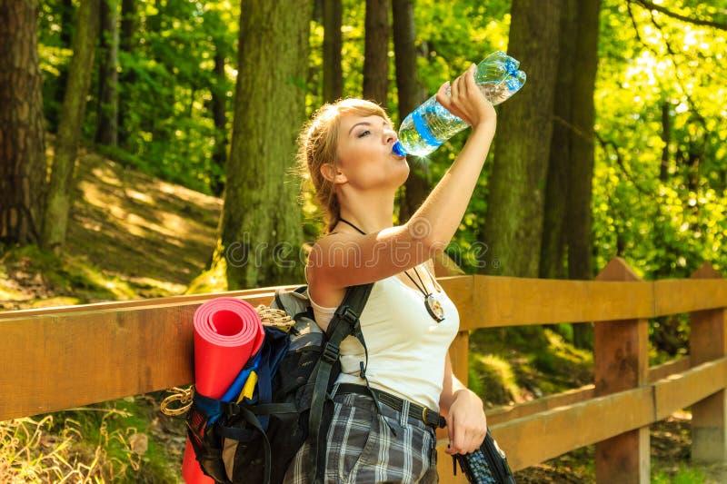 Młoda kobieta wycieczkuje w lasowym śladzie z plecakiem fotografia stock