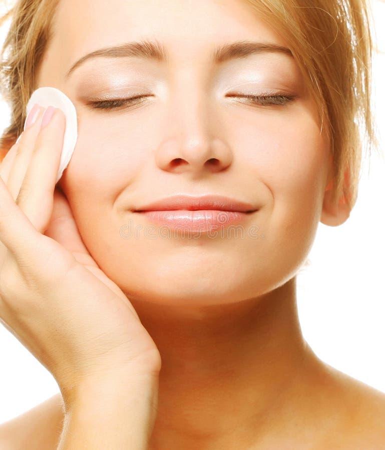 Młoda kobieta wyciera twarzy skórę obrazy stock