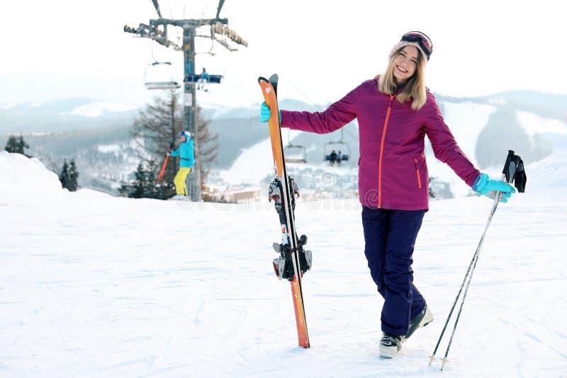 Młoda kobieta wydaje zima wakacje przy halnym kurortem z narciarskim wyposażeniem obrazy stock