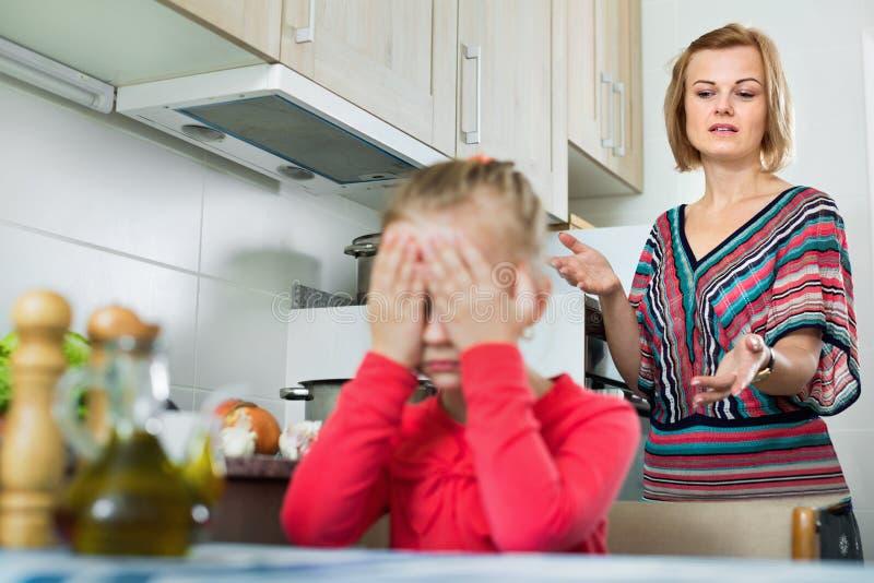Młoda kobieta wygłasza kazanie małej córki obrazy stock